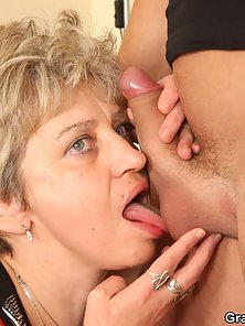Blonde Granny Enjoying Sex with Two Hunky Guys on Black Sofa
