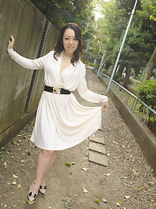 Asian Yuna Yamami walks in a white dress outside