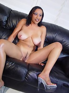 Busty ebony babe shows off pussy on couch