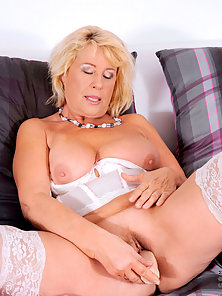 Hot and horny blonde mature dame stuffs her moist twat with the big dildo