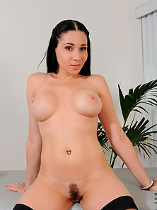 Horny black haired chick in stockings plays with her pussy