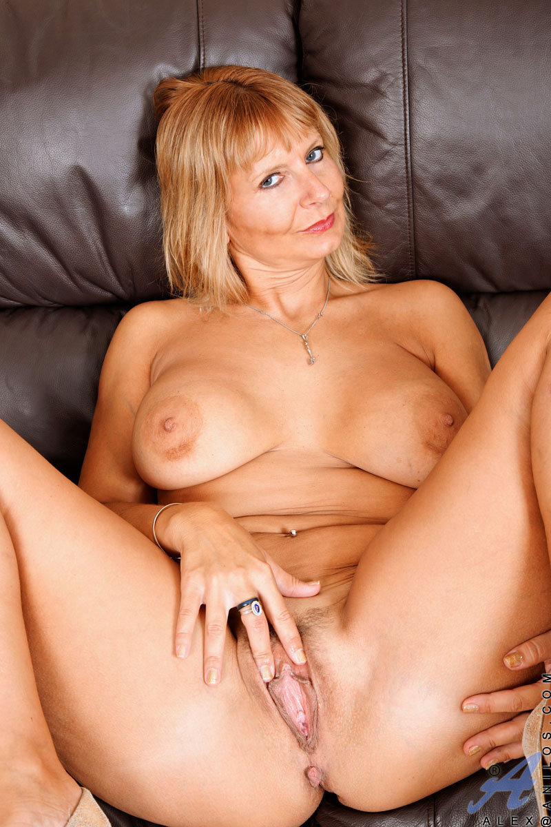 Busty Spreading busty babe spreading legs for pussy showing over black couch