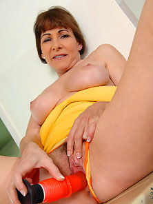 Attractive mature rides her dildo in front of the camera