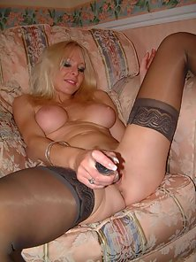 Sexy busty milf in stockings masturbates on the chair