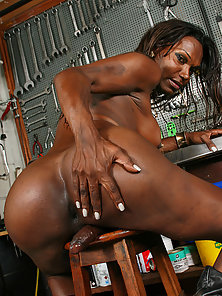 Muscular shemale Julia Anapolis poses her sexy black body and jerks in the garage