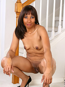Black milf seductress gets nude and parts her legs showing her sweet pink pussy
