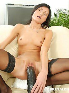 Brunette short haired babe plows her pussy with a huge dildo