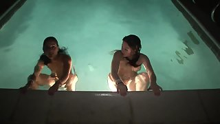 Two busty babes swimming naked in the pool at night