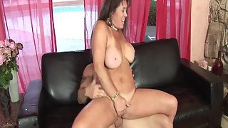 Busty brunette MILF takes care of lover's dick