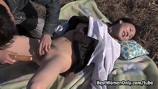 Asian babe gets a hard dildo in her pussy outdoors