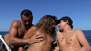 Curly haired brunette gets fucked by two guys on the beach