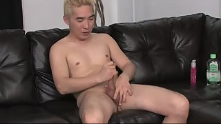 Asian twink solo jerking on leather couch